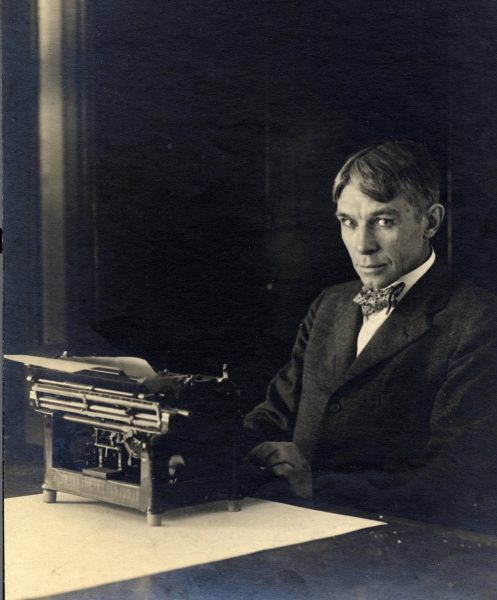 Photograph of Carl Sandburg sitting with his typewriter at his home in Illinois, circa 1917-1918.