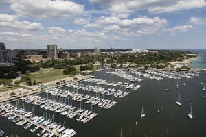 Photograph featuring an aerial view of boats in the marina on Lake Michigan with Milwaukee in the background.