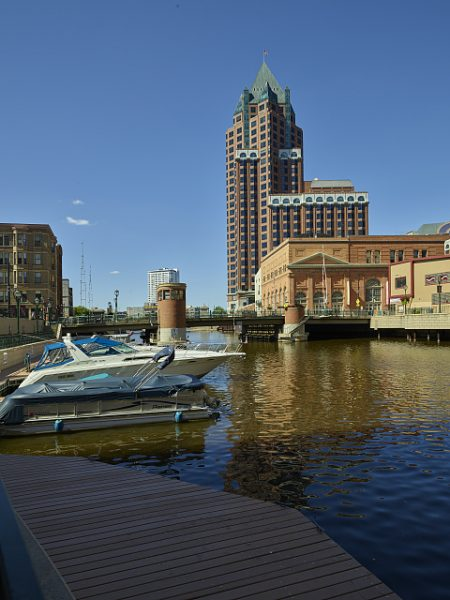 Photograph featuring a downtown view of the Milwaukee River with a boat docked in the foreground.