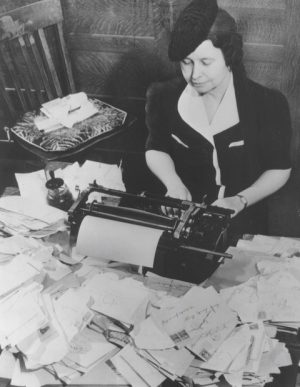 Photograph of Ione Quinby Griggs working at a typewriter during World War II.