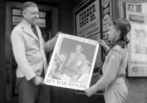 A Boy Scout helps display a poster promoting the purchase of war bonds in this 1943 photograph.
