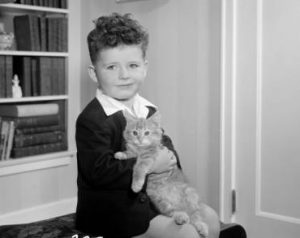 Photograph of a young boy in his home holding a cat, taken in 1948.