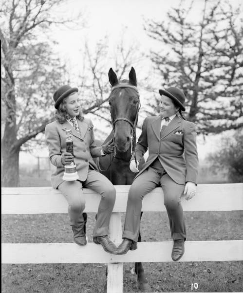 Photograph of two girls sitting on a fence with a horse, dated 1949. The girl on the left holds a small trophy.