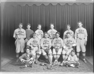 Group photograph of the 1929 Lincoln Avenue Merchants baseball team posed with a trophy.