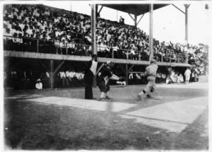 Photograph of spectators watching a baseball game between the Kosciuszko Reds and the Peters Union Giants in 1912.