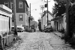 A 1970 photograph of an alley near Park Place and Bartlett Avenue showing parked automobiles and utility wires.