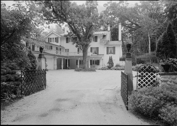 Photograph of the Ten Chimneys property looking south through the driveway gate.