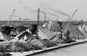 Snow covers piles of coal, with cranes in the foreground and smokestacks in the background, in this 1972 photograph.