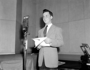 "A radio announcer stands behind a microphone during a broadcast of the WTJM radio program called ""Rumpus Room"" in 1945. The program featured advertisements for local retailers like Boston Store."