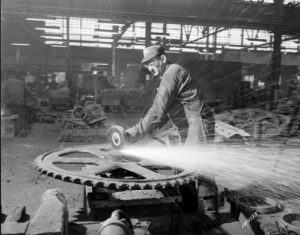 Photograph of a man grinding a large steel part at Pelton Steel Casting Company in 1956.