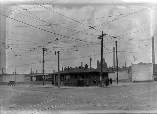 People wait for a streetcar in this 1932 photograph showing a station, the tracks embedded in the street, and the electrical network overhead.
