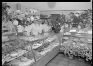 Women working for the Royal Baking Company, located on South 9th Street, stand behind display cases of baked goods in 1940.