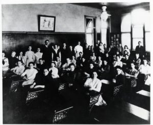 Photograph of Golda Meir and her 8th grade class taken at the 4th Street Elementary School in 1911. Meir is seen at the extreme right in a white dress.