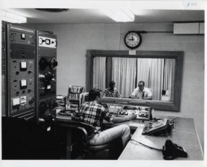 Photograph showcasing the radio booth and production of a WUWM broadcast, taken between 1978 and 1980.