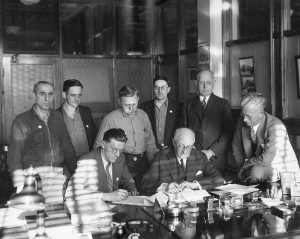 Harold Christoffel (seated, left) and Harold Story (seated, right) sign a contract surrounded by fellow Allis-Chalmers employees and managerial representatives.