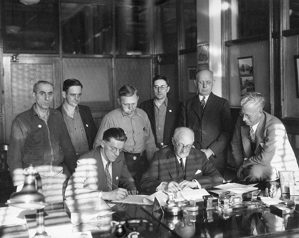 <table class=&quot;lightbox&quot;><tr><td colspan=2 class=&quot;lightbox-title&quot;>Coming to an Agreement</td></tr><tr><td colspan=2 class=&quot;lightbox-caption&quot;>Harold Christoffel (seated, left) and Harold Story (seated, right) sign a contract surrounded by fellow Allis-Chalmers employees and managerial representatives. </td></tr><tr><td colspan=2 class=&quot;lightbox-spacer&quot;></td></tr><tr class=&quot;lightbox-detail&quot;><td class=&quot;cell-title&quot;>Source: </td><td class=&quot;cell-value&quot;>From the Milwaukee County Historical Society. Found in the Harold Willis Story Papers, Box 5. <br /><a href=&quot;https://milwaukeehistory.net/research/photographic-collections/&quot; target=&quot;_blank&quot;>Milwaukee County Historical Society</a></td></tr><tr class=&quot;filler-row&quot;><td colspan=2>&nbsp;</td></tr></table>