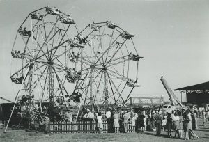 1941 photograph of crowds lined up around the twin Ferris Wheels at Milwaukee's Midsummer Festival.