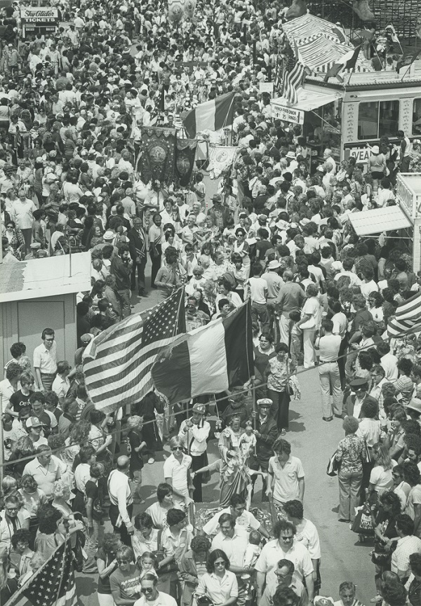 Photograph of the 1980 Festa Italiana procession winding through a crowd of people. The procession features flags, religious and cultural figures, and people in traditional clothing.