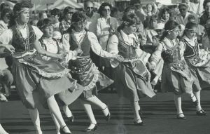 A group of six girls in traditional costumes dance at Greek Fest in 1984. Greek Fest is hosted by the Greek Orthodox Church of the Annunciation to celebrate Greek culture and community in Milwaukee.