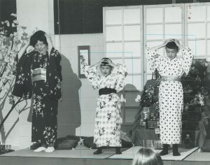 Two young boys and their mother perform a traditional Japanese song for school children gathered at the International Institute for Ethnic Spring Festival. The Japanese American Civic League was a member organization of the International Institute.