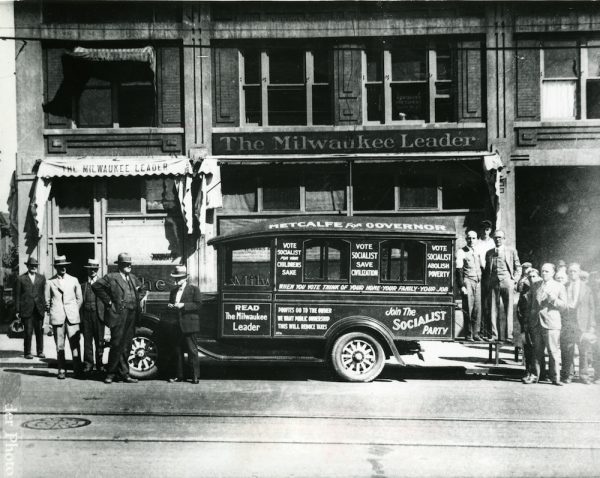 Men stand outside the office for the Milwaukee Leader in 1932. The paper's delivery truck is covered with messages promoting the Socialist Party.