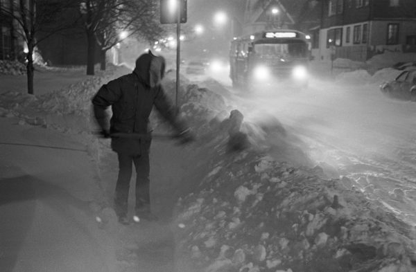 A figured bundled up against the cold shovels the sidewalk on a snowy night in December 1978.