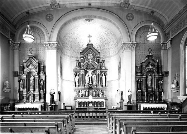 Taken in 1960, this photograph showcases the three altars located at the front of the Holy Trinity Our Lady of Guadalupe church.