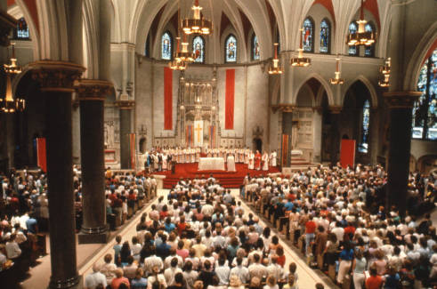 Photograph of the congregation standing at a Mass held in the Church of the Gesu.
