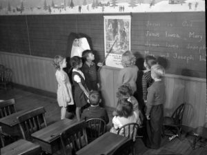 Photograph of a nun teaching a small group of children at St. Francis School in 1945.