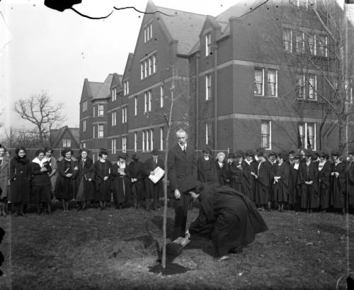 Milwaukee-Downer College graduates gather outside to plant a tree as part of the commencement ceremony in 1922 .