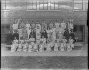 A group portrait of children in costumes and nuns at the St. Joseph Orphanage in 1921.