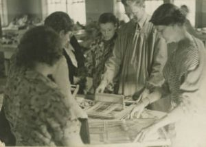 Individuals learn to weave as part of the Works Progress Administration's Milwaukee Handicraft Project, which provided light manufacturing work for unskilled workers.