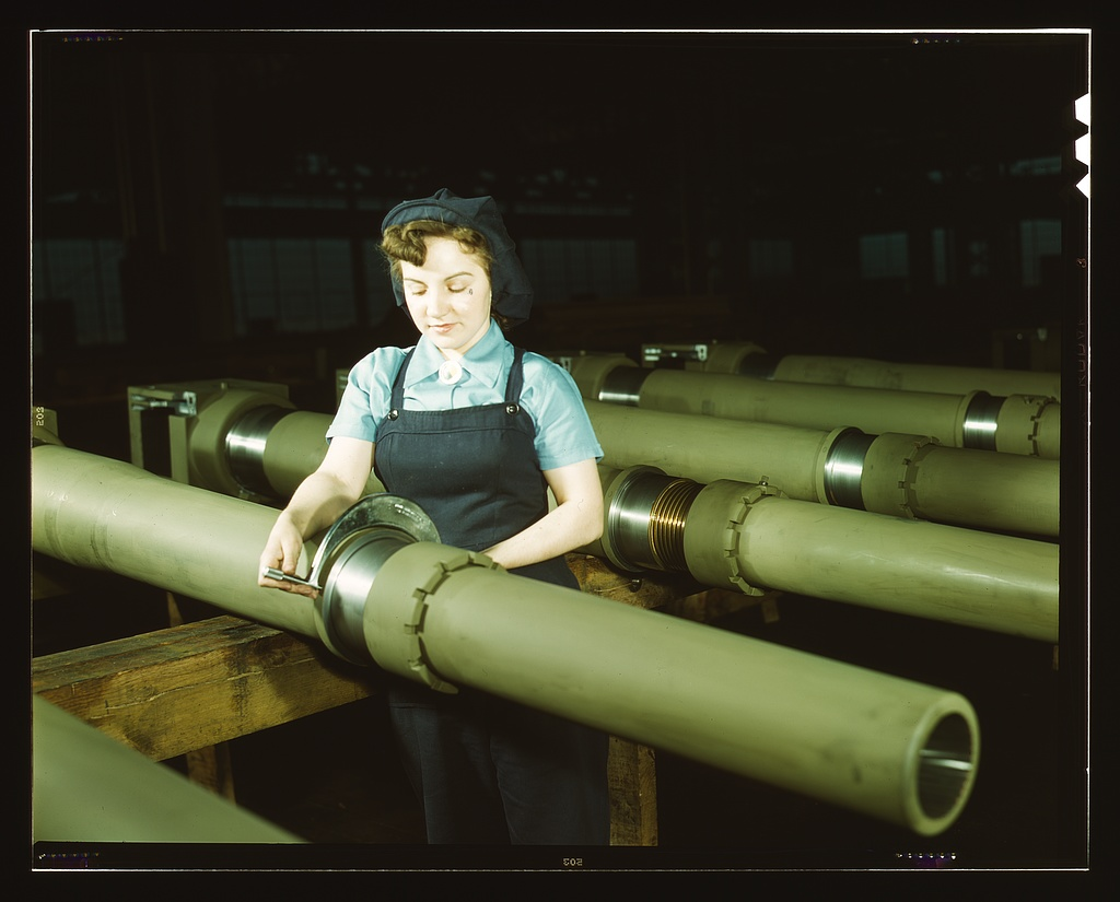During World War II, the Chain Belt Company manufactured howitzers. Taken in 1943, this photo shows a female employee inspecting a howitzer component for metal burrs.