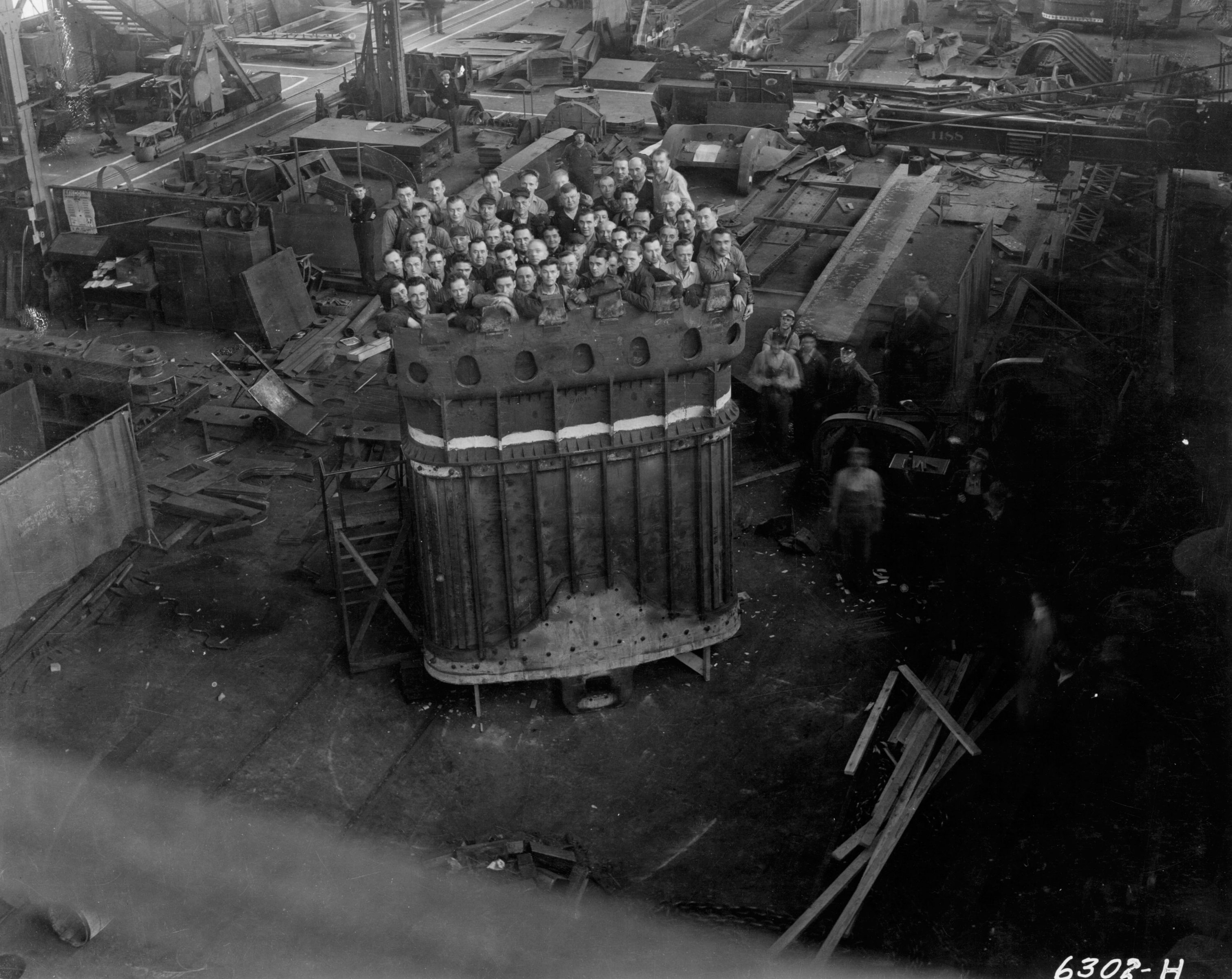 52 men stand inside a massive dipper for a 950B stripping shovel manufactured at the Bucyrus-Erie plant in South Milwaukee.