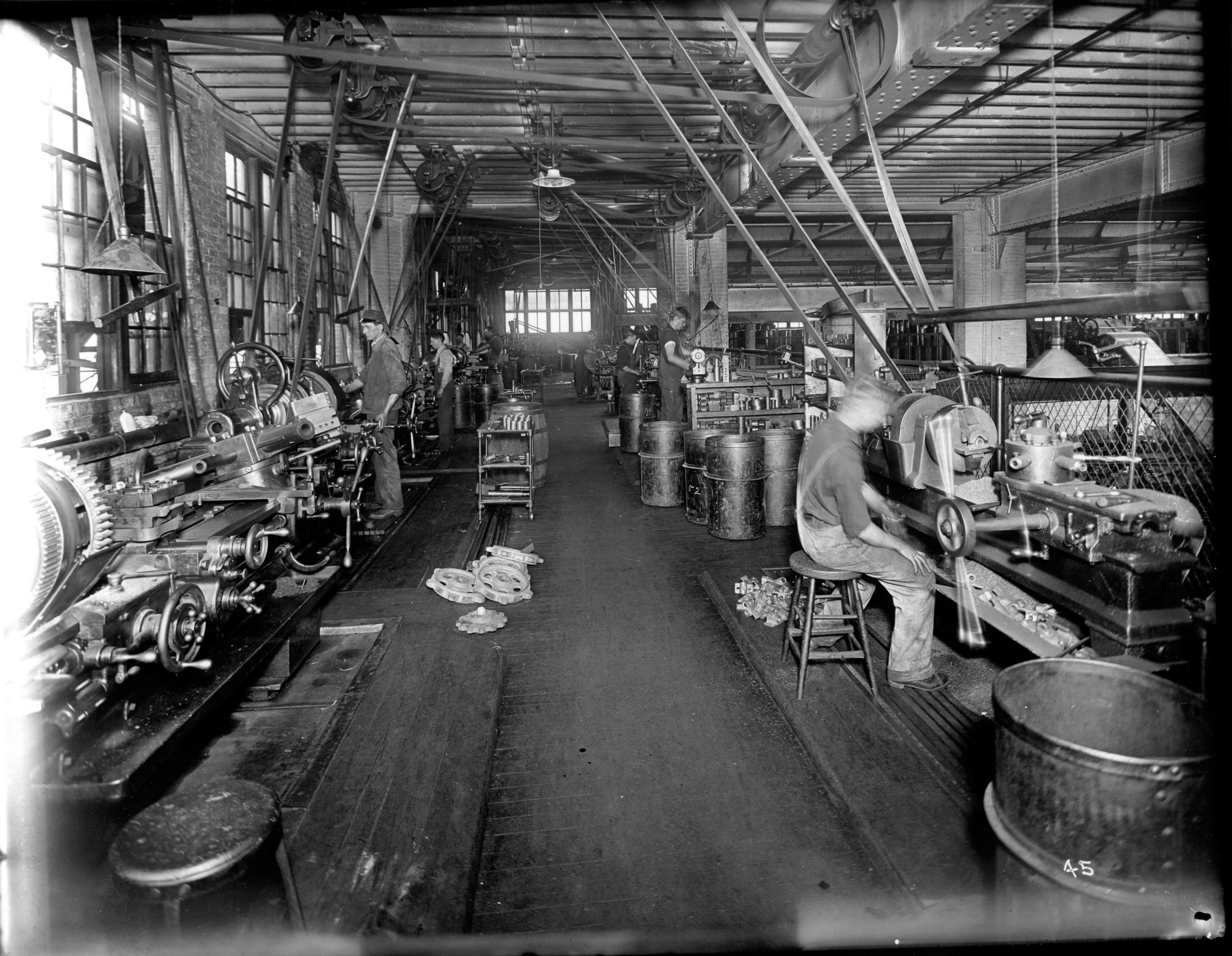Chain Belt Company employees work at metal lathes. Finished parts and gears are stacked behind the men.