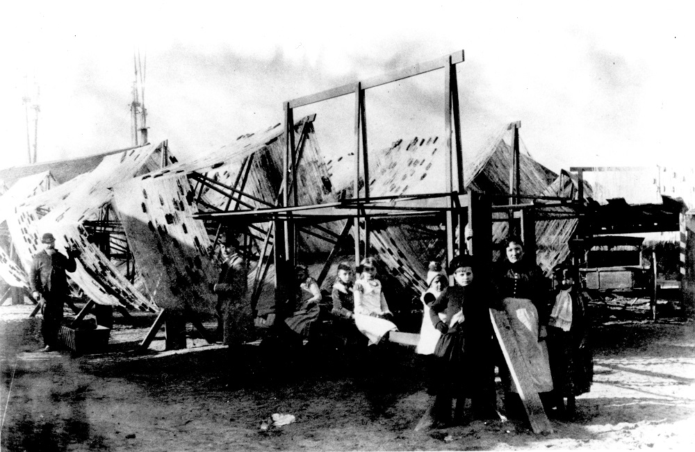 Jones Island residents stand in front of large fishing nets stretched out to dry.