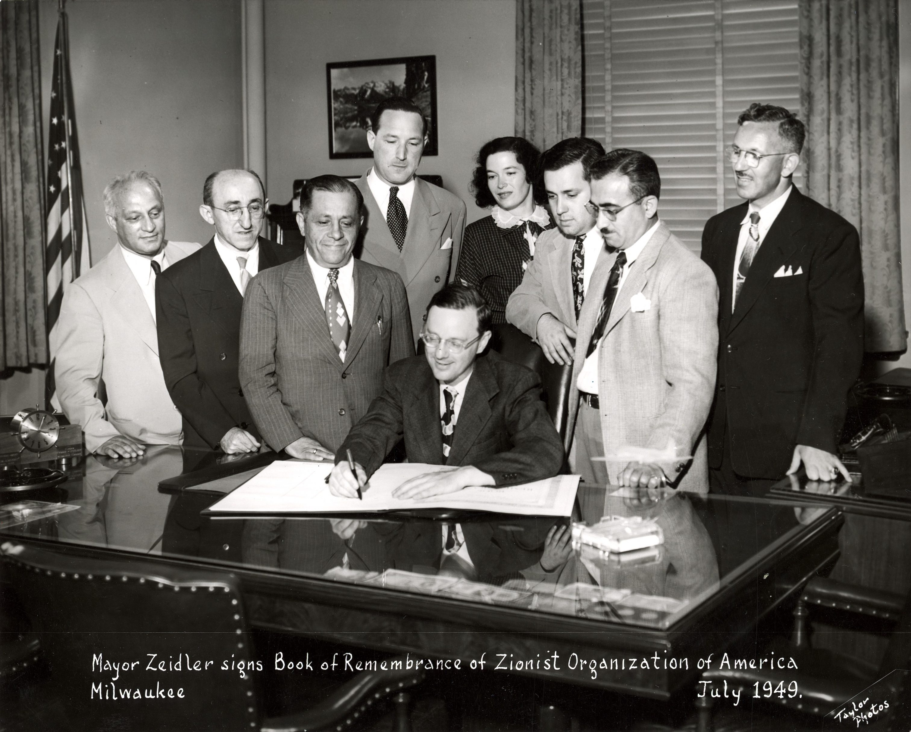 Mayor Frank Zeidler signs a Book of Remembrance while members of the Zionist Organization of America look on in this 1949 photograph.