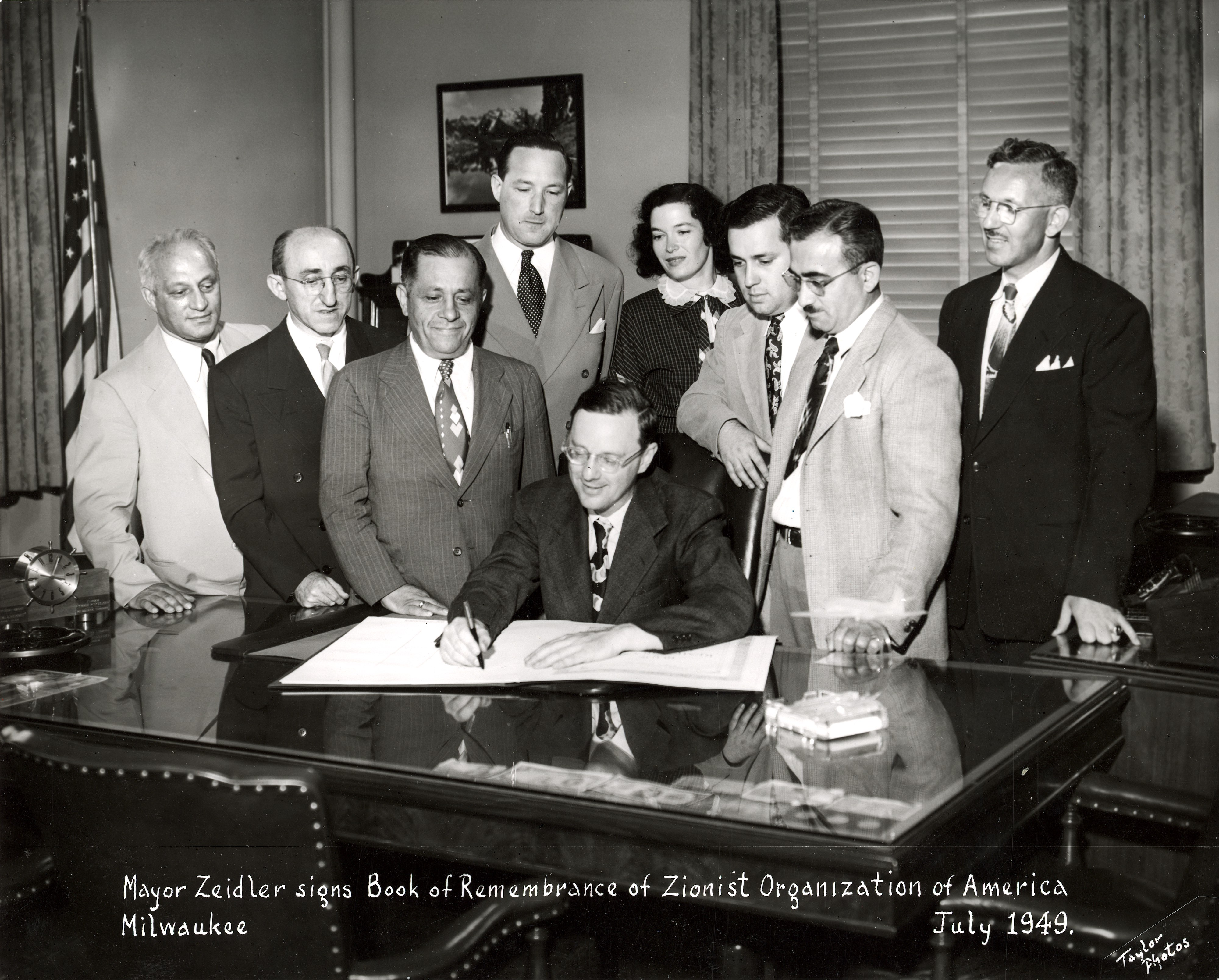 <table class=&quot;lightbox&quot;><tr><td colspan=2 class=&quot;lightbox-title&quot;>Frank Zeidler Signs Book of Remembrance</td></tr><tr><td colspan=2 class=&quot;lightbox-caption&quot;>Mayor Frank Zeidler signs a Book of Remembrance while members of the Zionist Organization of America look on in this 1949 photograph.</td></tr><tr><td colspan=2 class=&quot;lightbox-spacer&quot;></td></tr><tr class=&quot;lightbox-detail&quot;><td class=&quot;cell-title&quot;>Source: </td><td class=&quot;cell-value&quot;>From the Milwaukee Mayors Collection of the Milwaukee Public Library. Reprinted with permission.<br /><a href=&quot;http://content.mpl.org/cdm/singleitem/collection/MilwMayors/id/112/rec/8&quot; target=&quot;_blank&quot;>Milwaukee Public Library</a></td></tr><tr class=&quot;filler-row&quot;><td colspan=2>&nbsp;</td></tr></table>