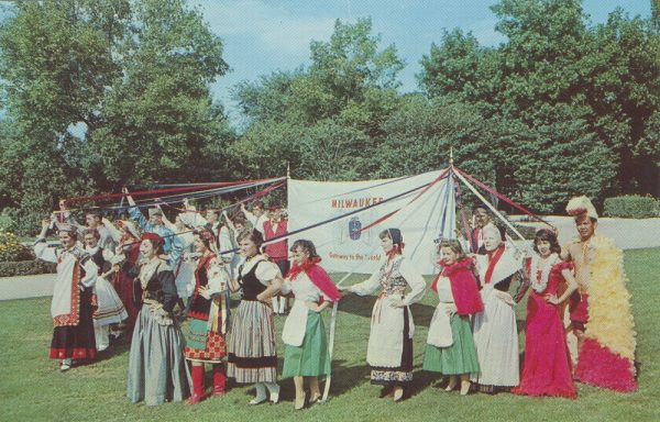 Men and women dressed in traditional costumes stand outside holding a banner during the Holiday Folk Fair.