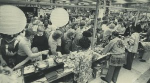 People stand in line to try ethnic foods at the Holiday Folk Fair, served by people in traditional dress, in 1982.