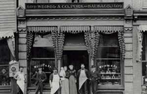Men and women stand in front of the Weisel & Company store, founded in 1878 and located on Water Street.