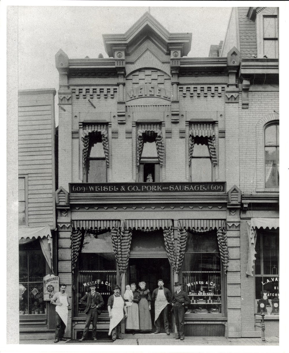 <table class=&quot;lightbox&quot;><tr><td colspan=2 class=&quot;lightbox-title&quot;>Weisel &amp; Company Store</td></tr><tr><td colspan=2 class=&quot;lightbox-caption&quot;>Men and women stand in front of the Weisel &amp; Company store, founded in 1878 and located on Water Street. </td></tr><tr><td colspan=2 class=&quot;lightbox-spacer&quot;></td></tr><tr class=&quot;lightbox-detail&quot;><td class=&quot;cell-title&quot;>Source: </td><td class=&quot;cell-value&quot;>From the Historic Photo Collection of the Milwaukee Public Library. Reprinted with permission. <br /><a href=&quot;http://content.mpl.org/cdm/singleitem/collection/HstoricPho/id/1314/rec/2&quot; target=&quot;_blank&quot;>Milwaukee Public Library</a></td></tr><tr class=&quot;filler-row&quot;><td colspan=2>&nbsp;</td></tr></table>