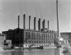 This undated photograph of the Wisconsin Electric Power plant shows coal barges transporting fuel on the Milwaukee River.