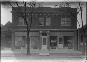 This photograph shows the offices of Valerian M. Popowski Real Estate and the Cudahy Savings and Loan Association, as well as a vacant storefront in the 1920s.
