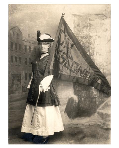 "Portrait of Wisconsin Woman Suffrage Association president Theodora Youmans standing in front of a painted backdrop holding an ""On Wisconsin"" flag in 1915."