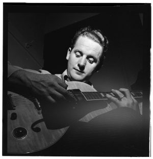 A younger Les Paul looks down at his guitar in this photograph from 1947.