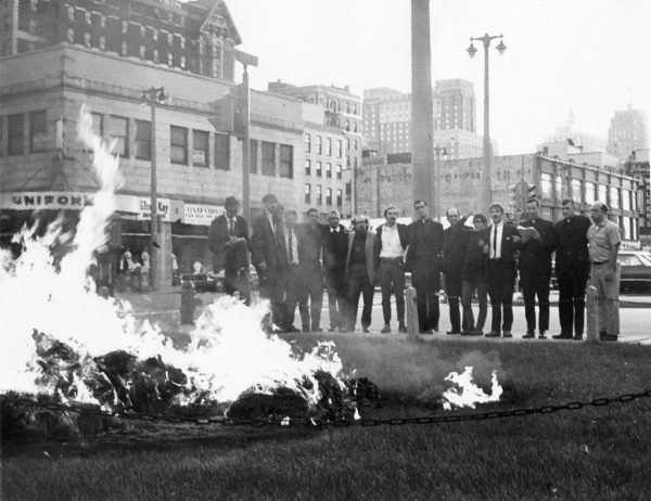 Photograph of the fourteen men (starting at the far right) who burned approximately 10,000 draft cards in 1968 standing arm-in-arm. The man furthest to the left is a newspaper reporter.