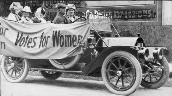 "Members of the Political Equality League are seated in an early model Ford car draped with a banner that reads ""Votes for Women."""