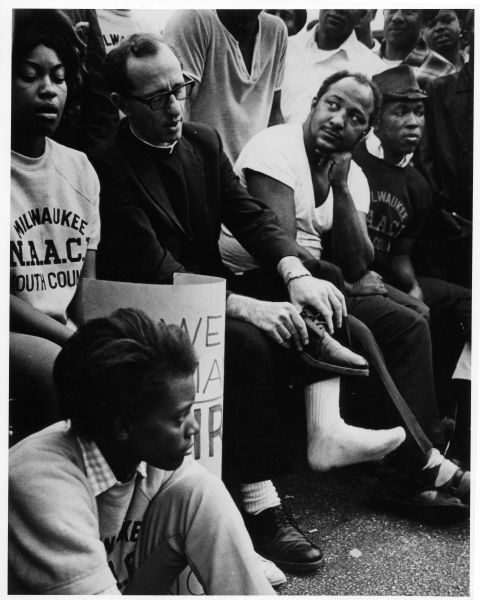 Father James Groppi rests with fellow marchers amid their demonstrations for fair housing in 1967.