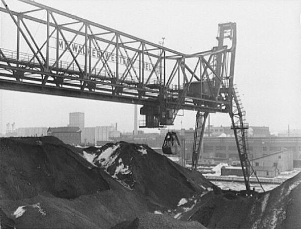 Photograph featuring a bridge at the Seventeenth Street dock of the Milwaukee Western Fuel Company in 1942. The bridge is used for unloading coal from ships and loading it into cars and hoppers.